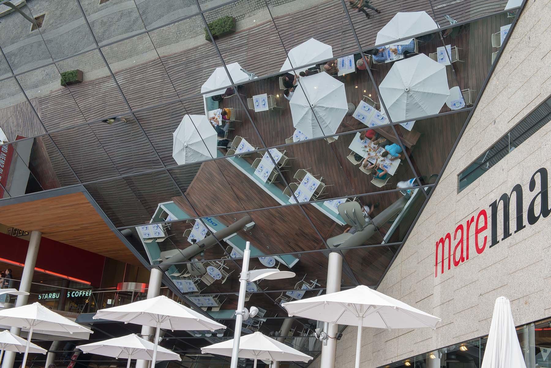 Odbicia białych parasolii w zabudowie centrum handlowegow Port Vell w Barcelonie