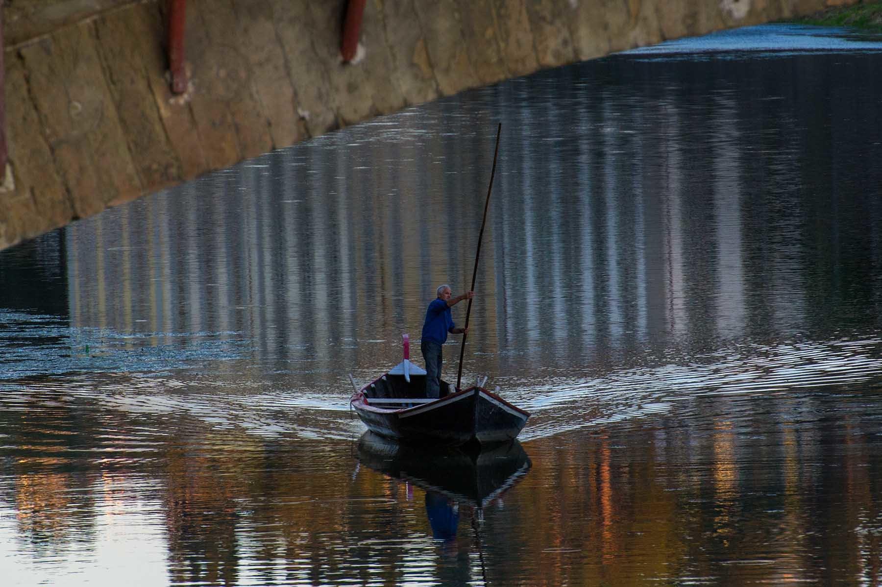 Człowiek płynący łodzią pod mostem na rzecze Arno we Florencji