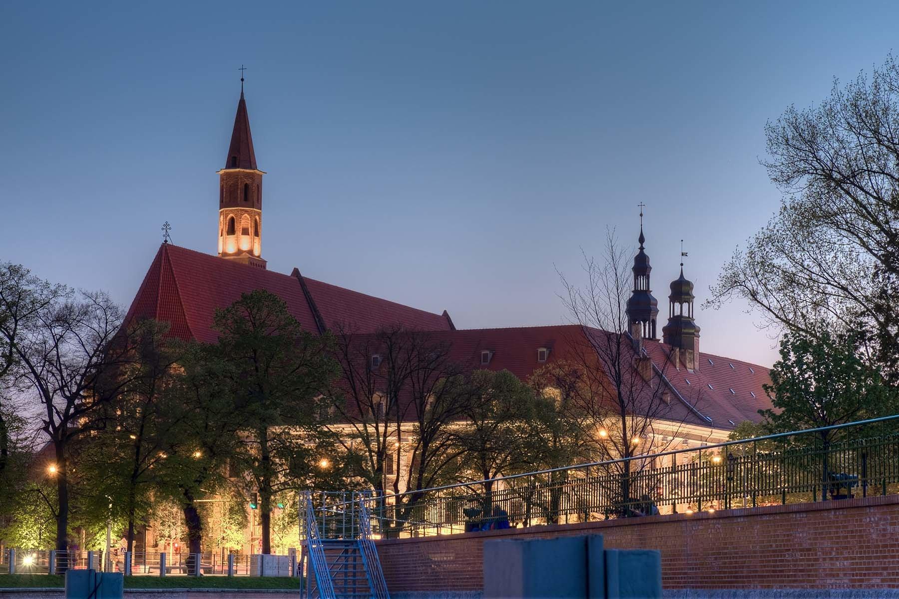 Instytut Filologii Polskiej Uniwersytetu Wrocławskiego wieczorową porą widziany z nadbrzeża Odry