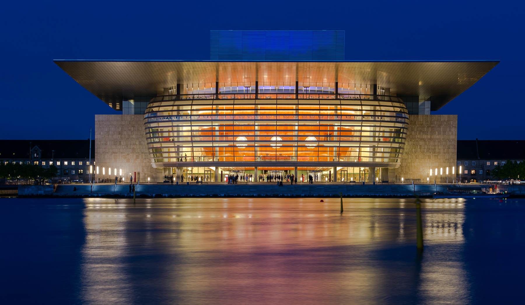 Rozświecony budynek Opery w Kopenhadze o niebieskiej godzinie.