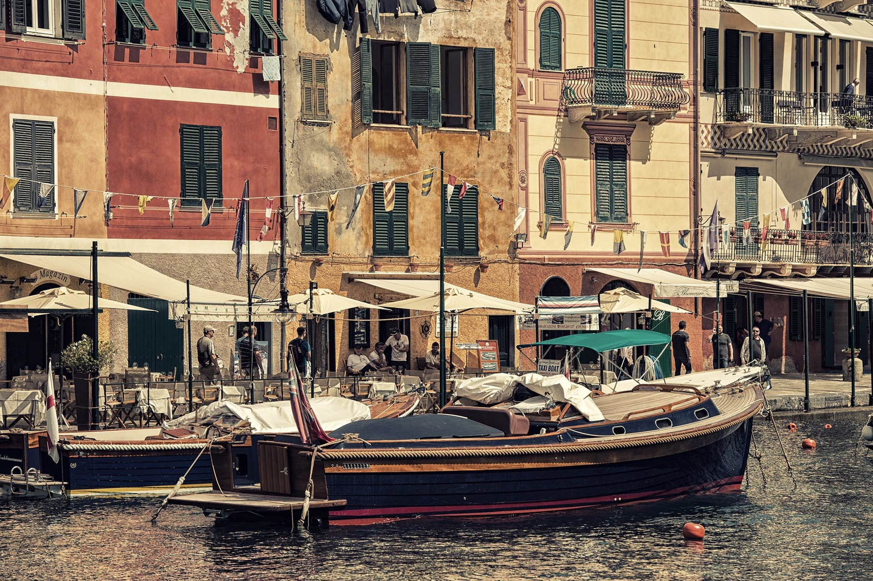 Cumująca łódż obok lolorowych portowych budynków Portofino