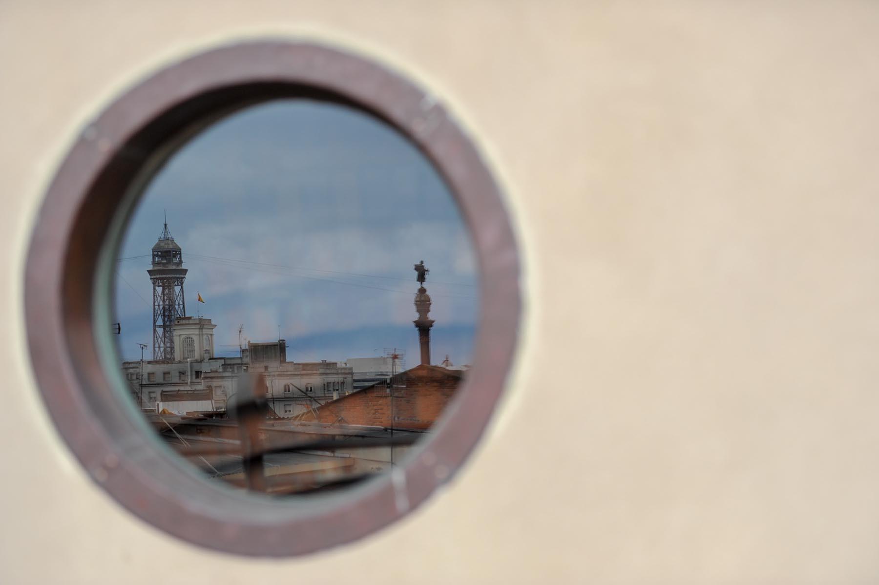 Dachy barcelony odbijające sie w oknie Pałacu Guell