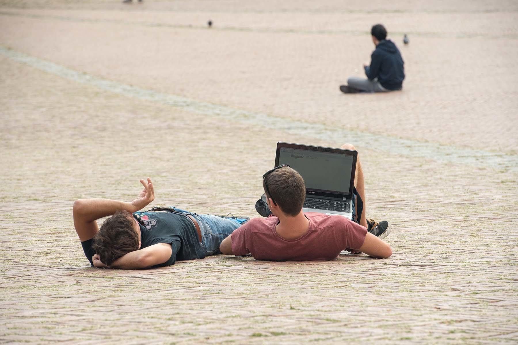 Ludzie siedzący i odpoczywający na Piazza del Campo w Sienie