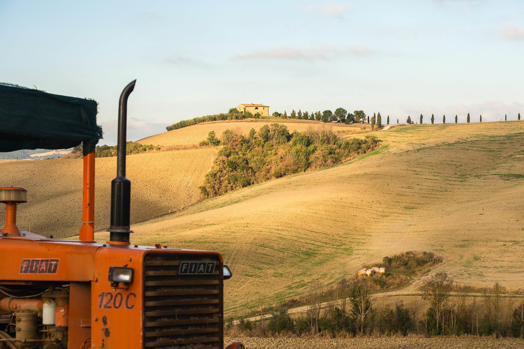 Czerwony traktor na toskańskich polach w ololicach Val d'Orcia