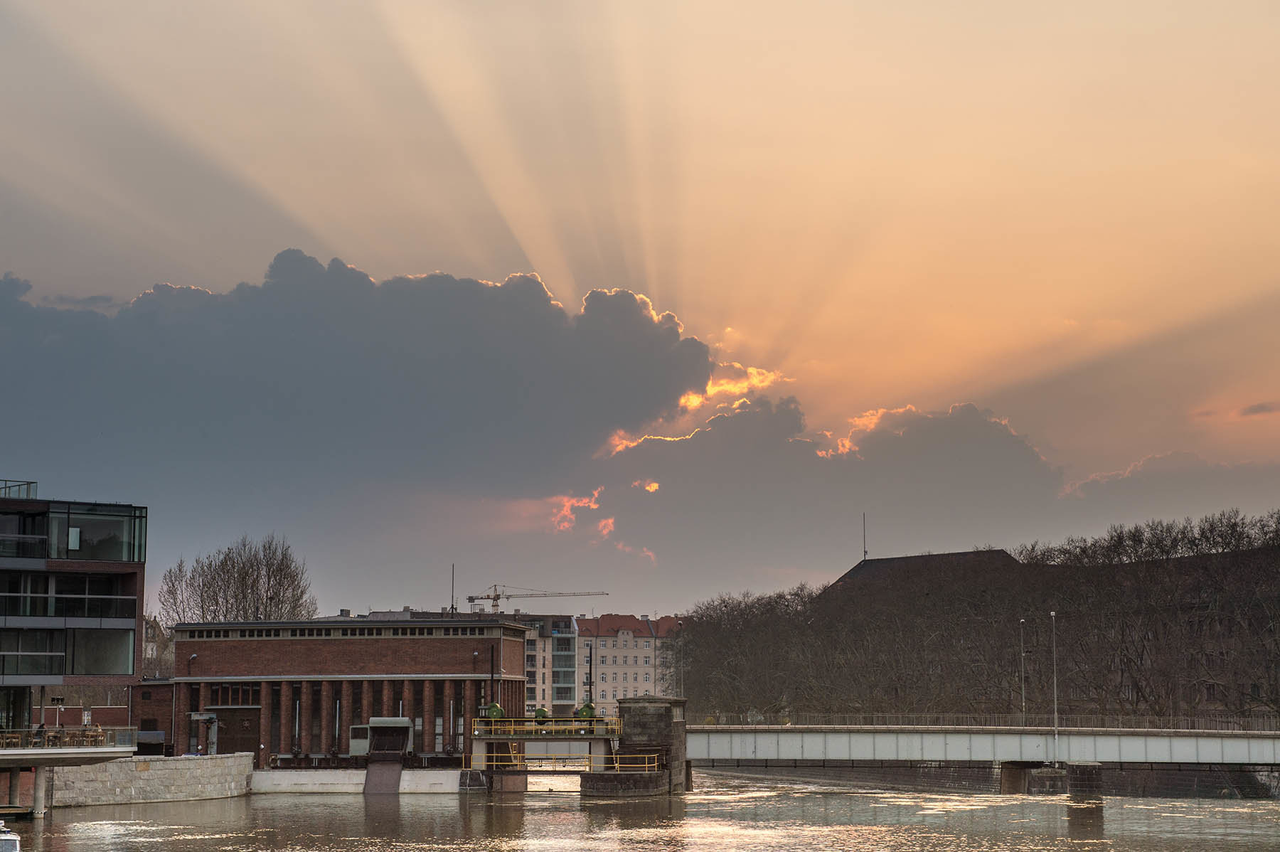 Zachodzące za chmurami słońce nad Odrą w centrum Wrocławia