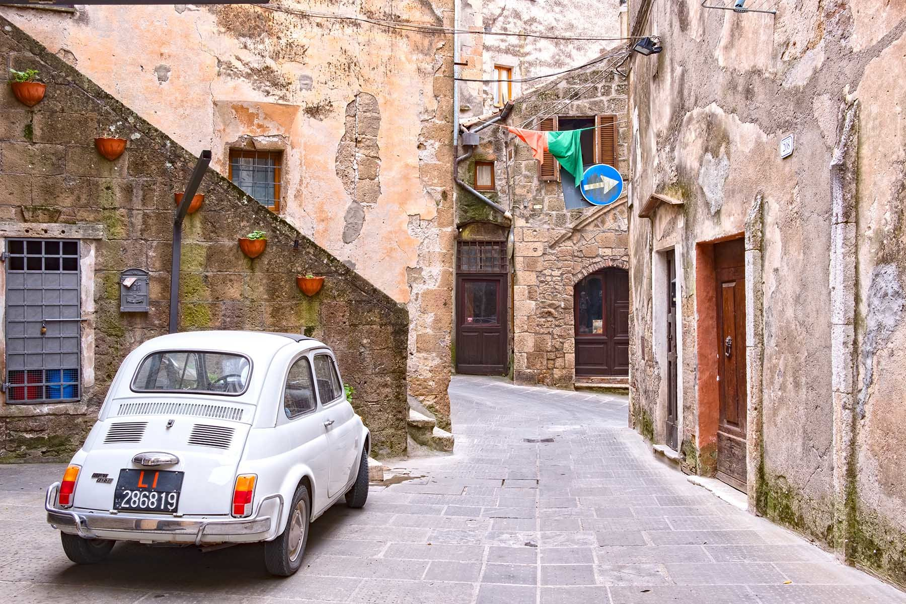 Biały stary Fiat 500 na uliczkach Pitigliano.